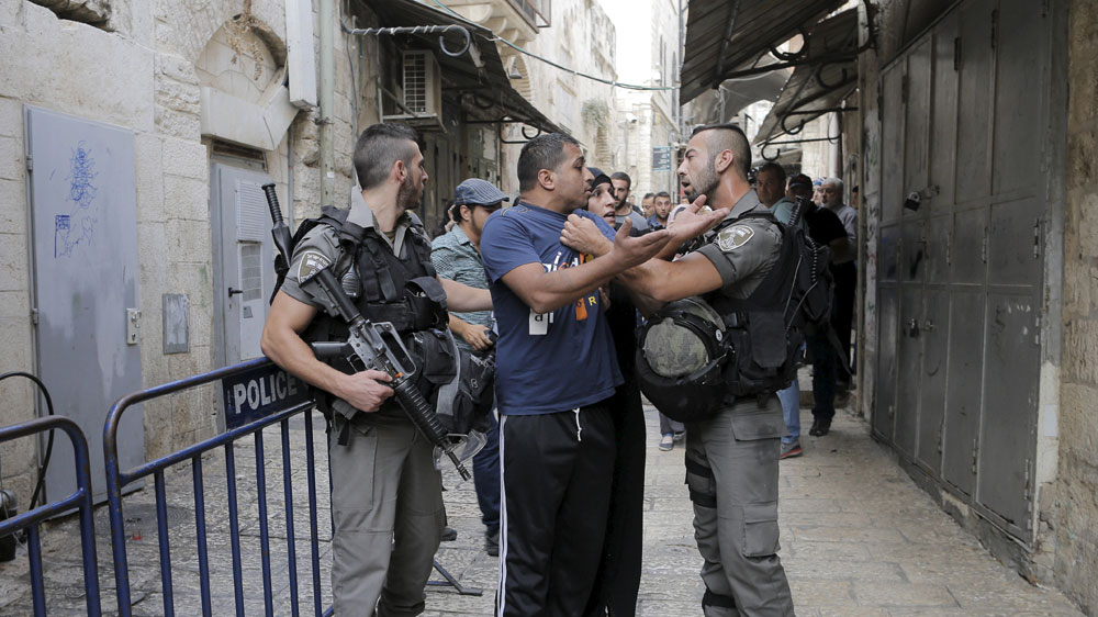 Israeli police officers detain a Palestinian protester in Jerusalem's Old City. [Ammar Awad/Reuters]