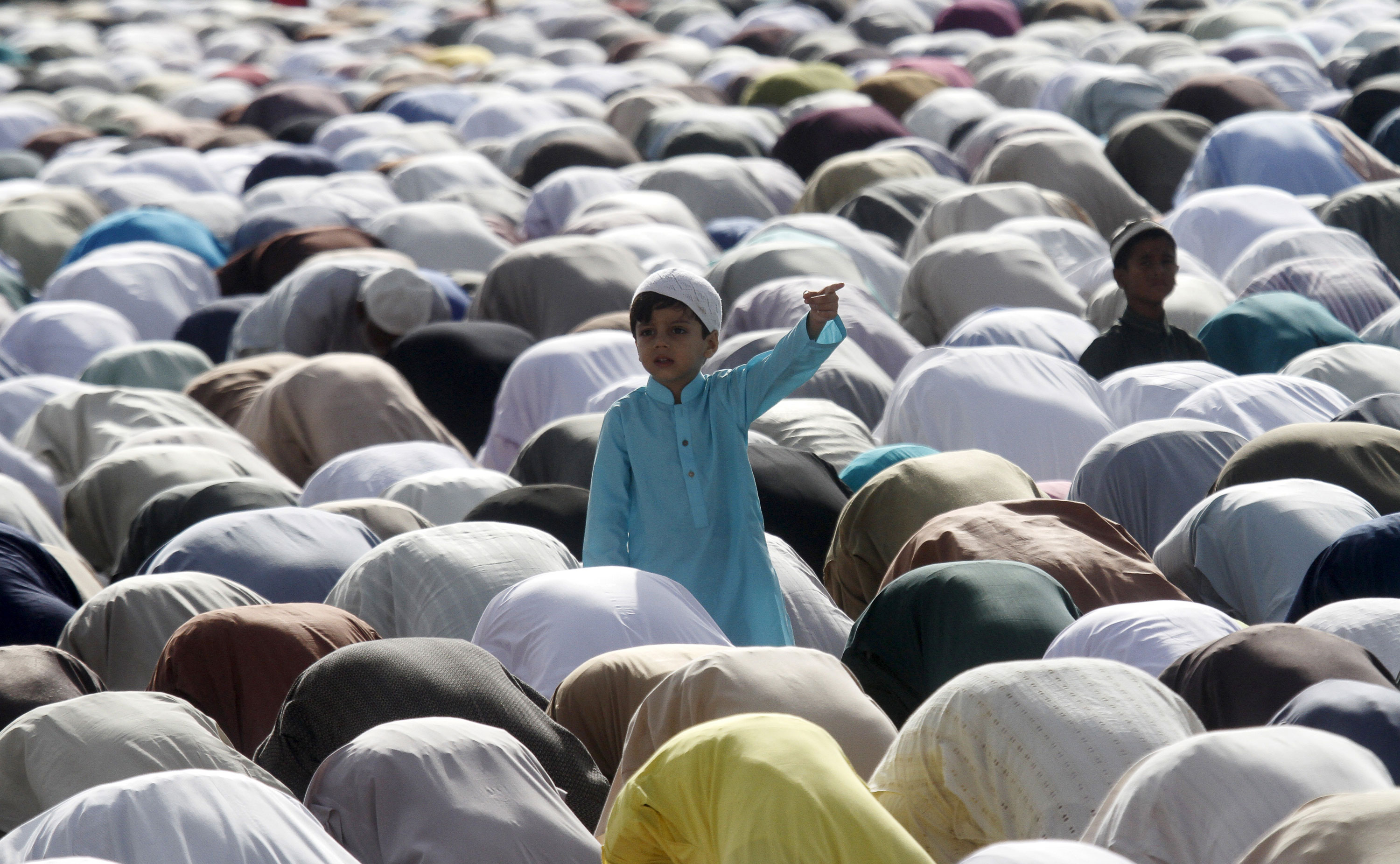 Muslims perform Eid prayers in Karachi, Pakistan. [Athar Hussain/Reuters]