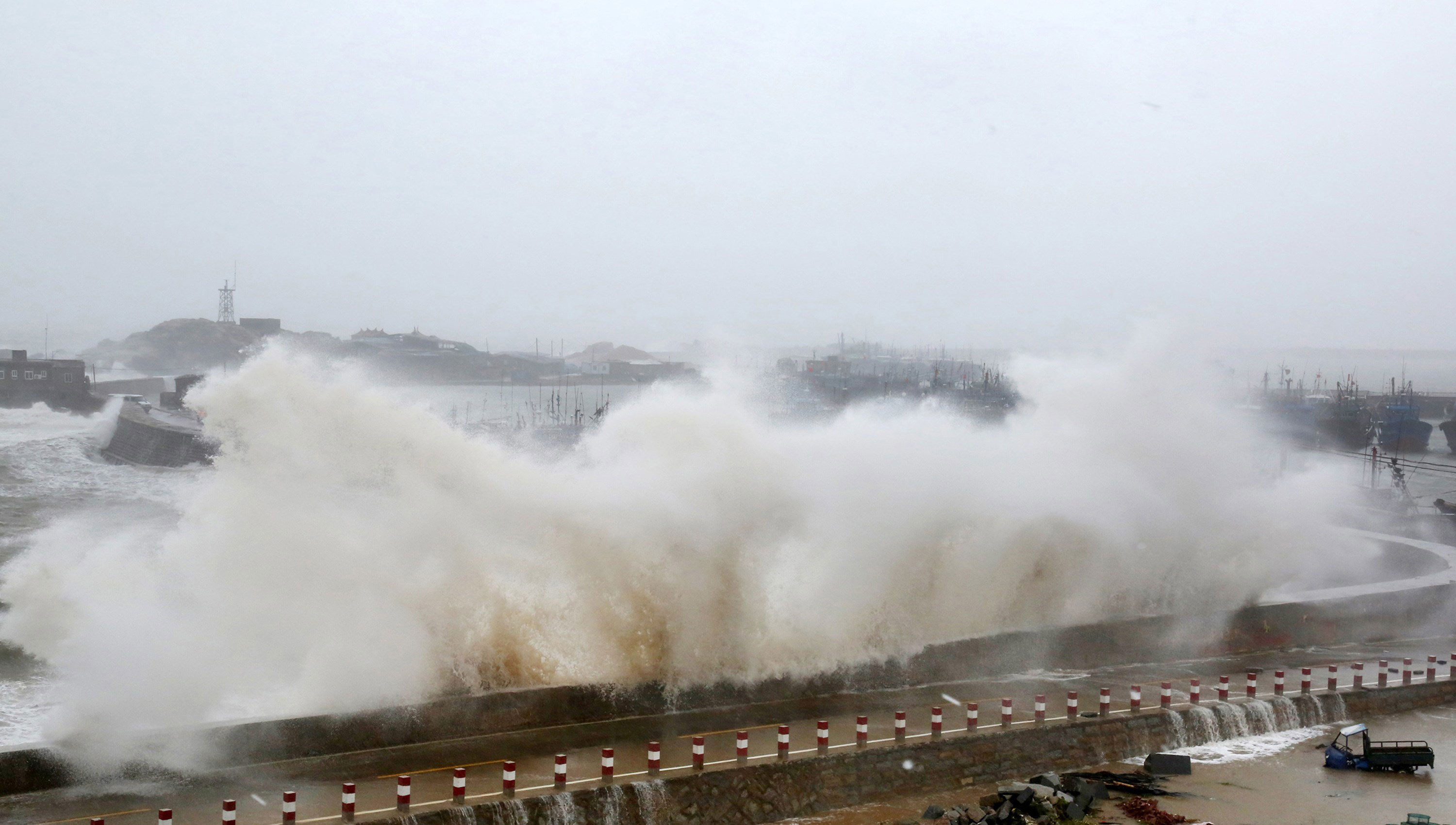 Waves crash into a pier in Huian county in Quanzhou in Fujian province of eastern China [China Out/AFP]