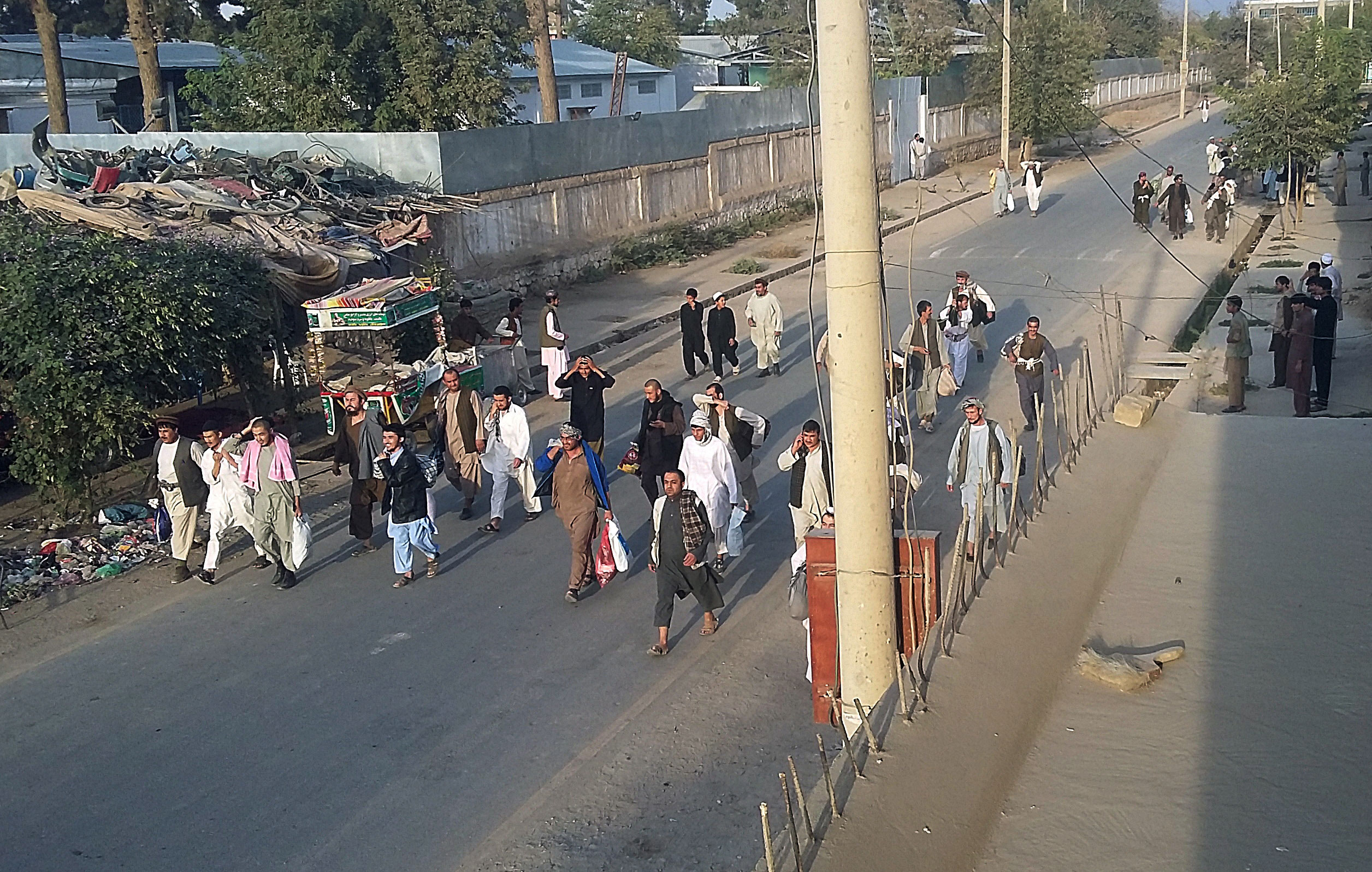 Taliban prisoners walked on a street after their comrades released them from the main jail in Kunduz on Monday [AP]