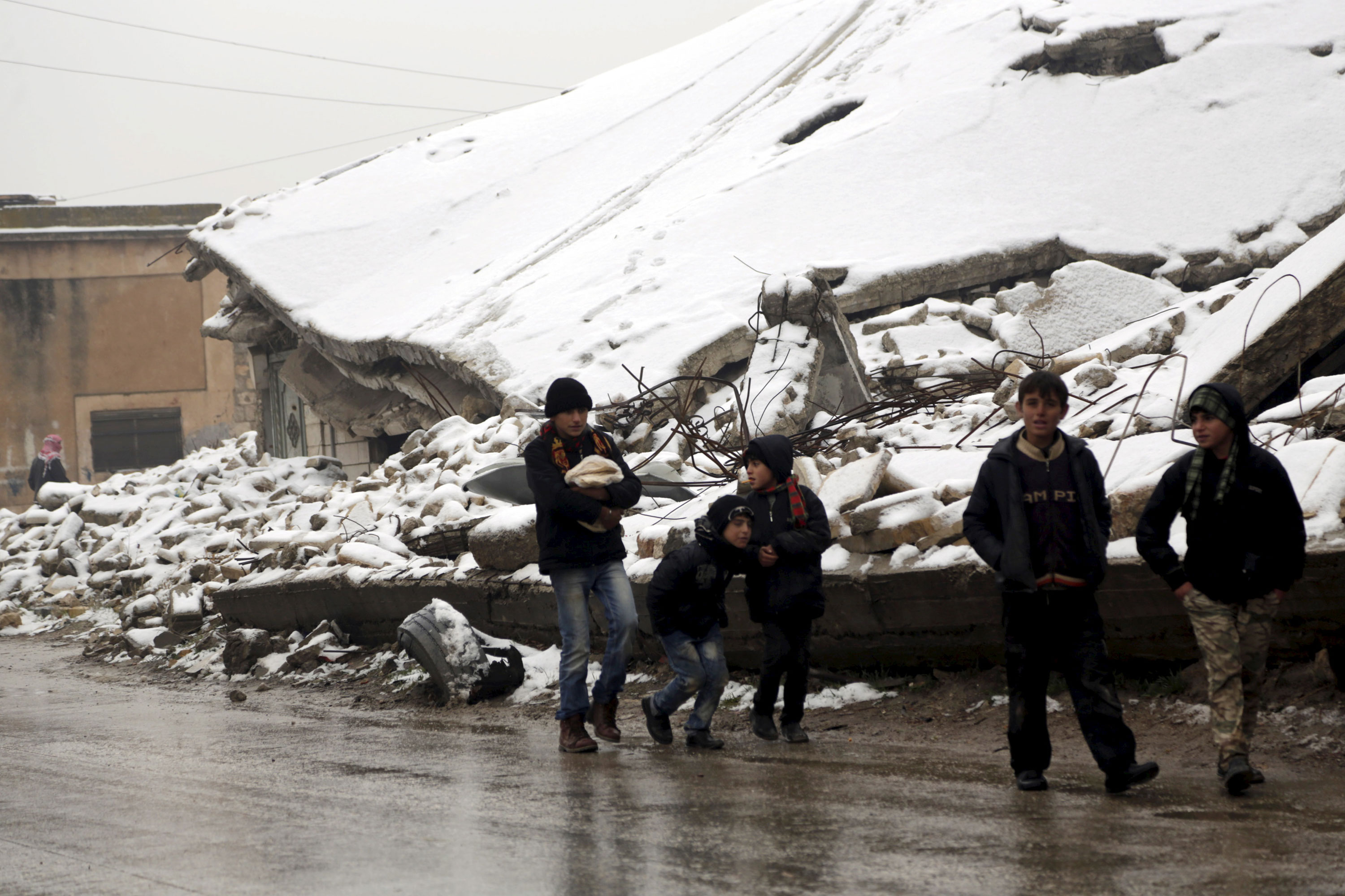 Boys walk past damaged buildings covered with snow in the rebel-controlled area of Maaret al-Numan town in Idlib province, Syria. [Khalil Ashawi/Reuters]