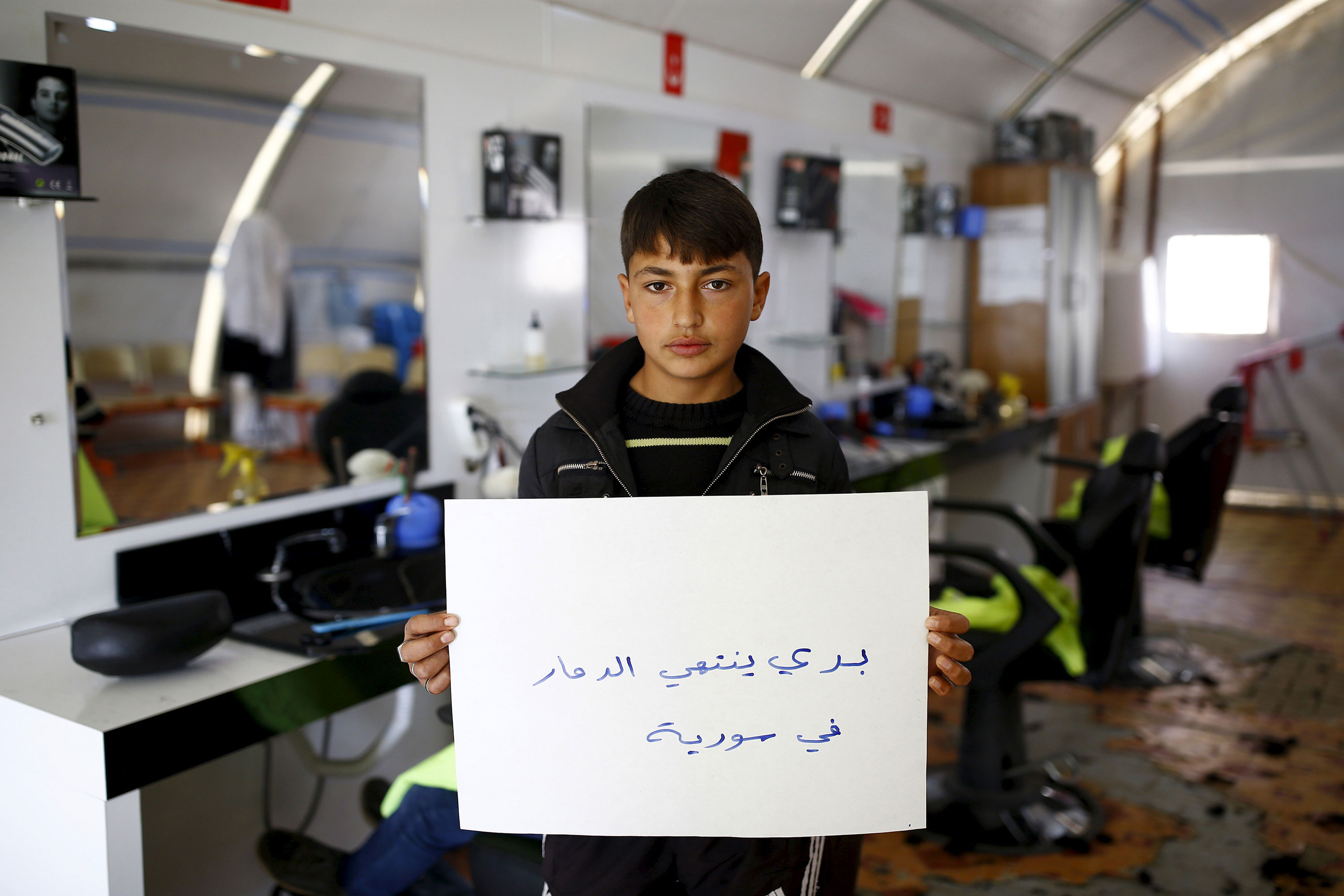 "Abdullah El-Omer, 15, poses with a sign that says: ""I want an end to the destruction in Syria,"" at a barber shop where he works in the Midyat refugee camp in Mardin province, Turkey. [Umit Bektas/Reuters]"