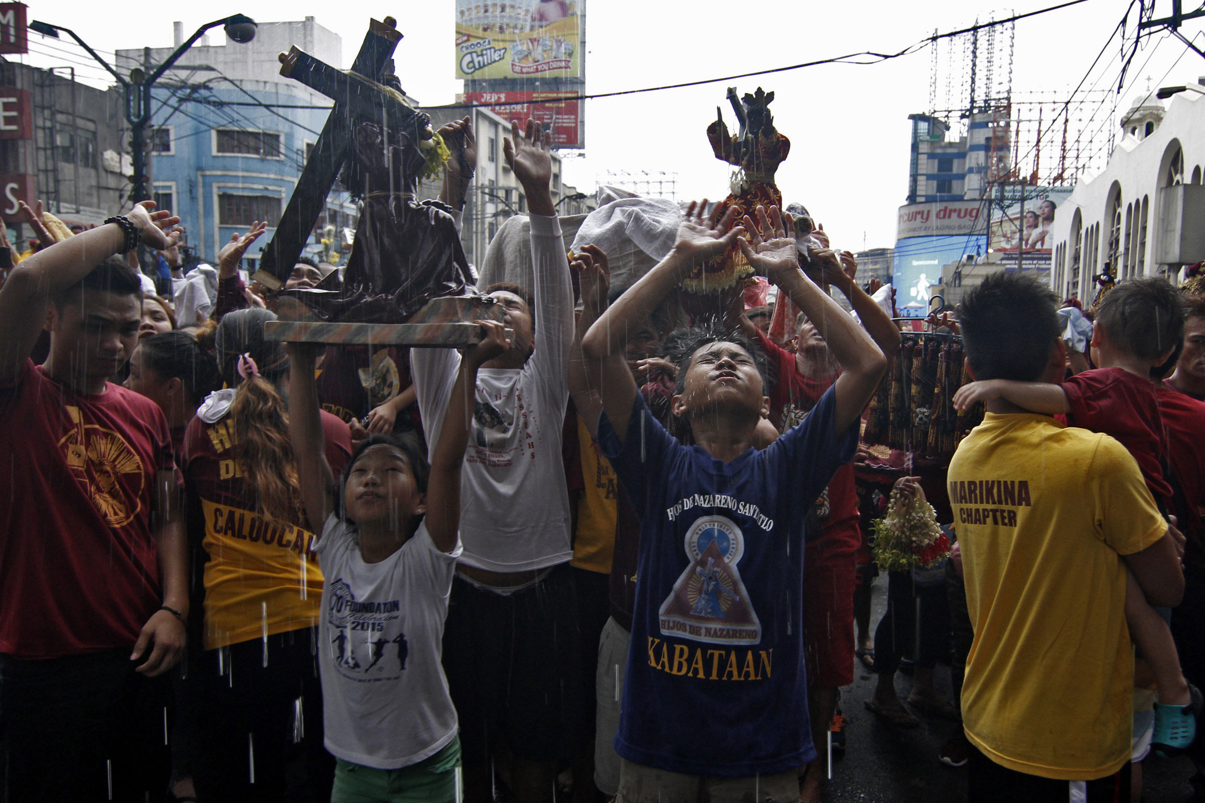 Thousands of devotees and Black Nazarene replicas are blessed with holy water from a position above the streets outside the Minor Basilica in Quiapo, Manila, on January 7 before the procession of the Black Nazarene. [Vincent Go/Al Jazeera]