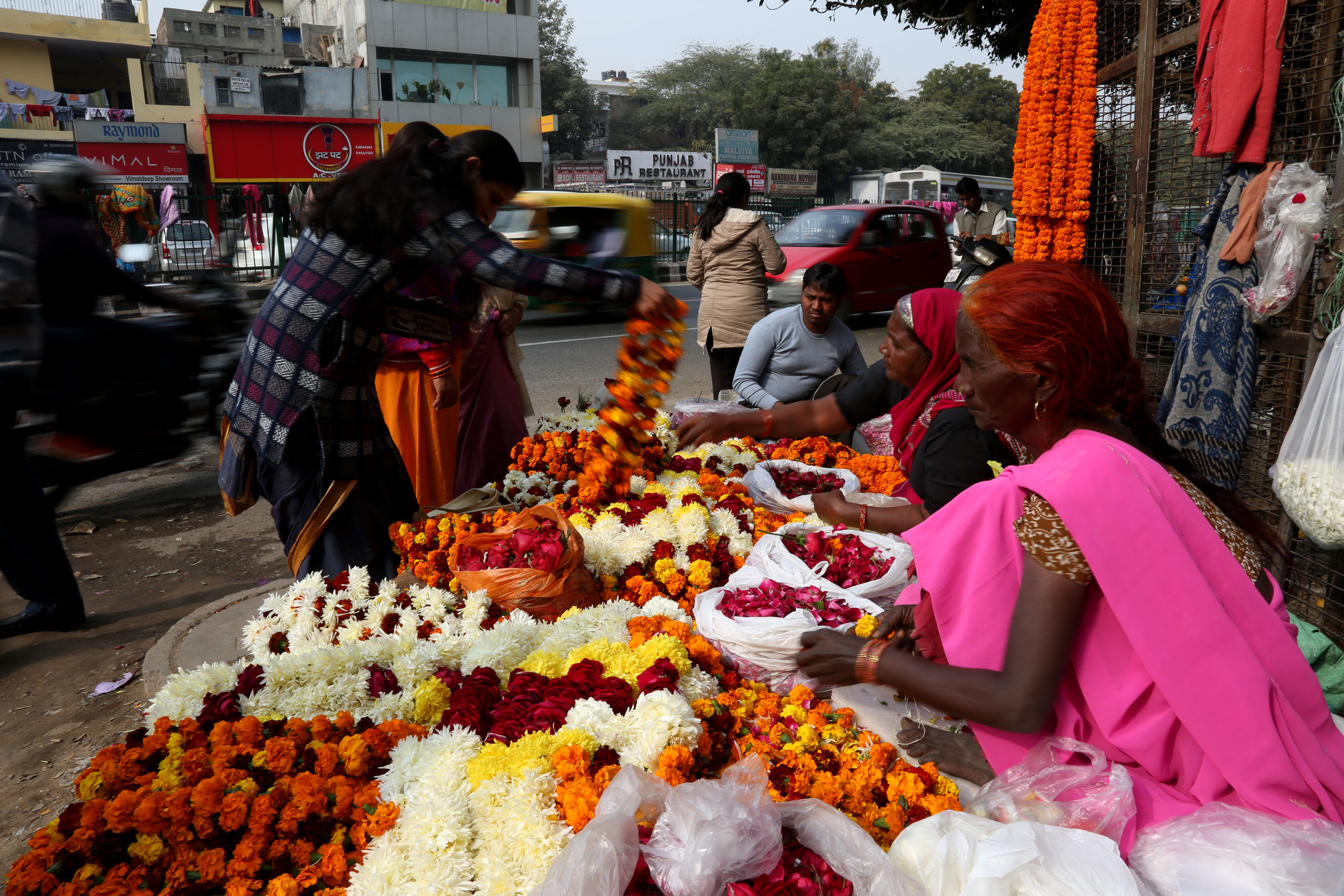 "Mahesh and his family has sold flower garlands on same spot for the last 30 years. ""It will be great if we get the licences,"" Mahesh said [Showkat Shafi/Al Jazeera]"