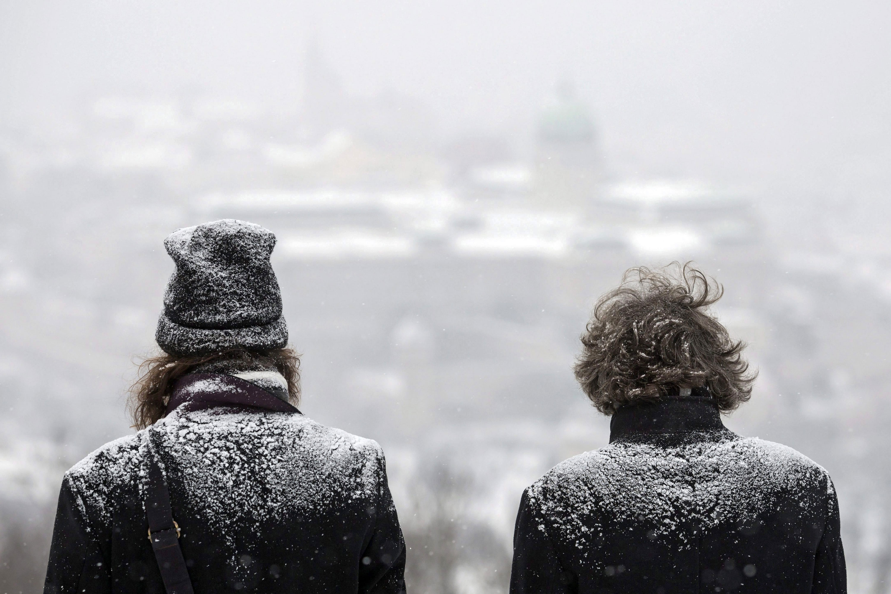 Two men look over Buda Castle during snowfall atop Gellert Hill in Budapest, Hungary. [Balazs Mohai/Hungry Out/EPA]
