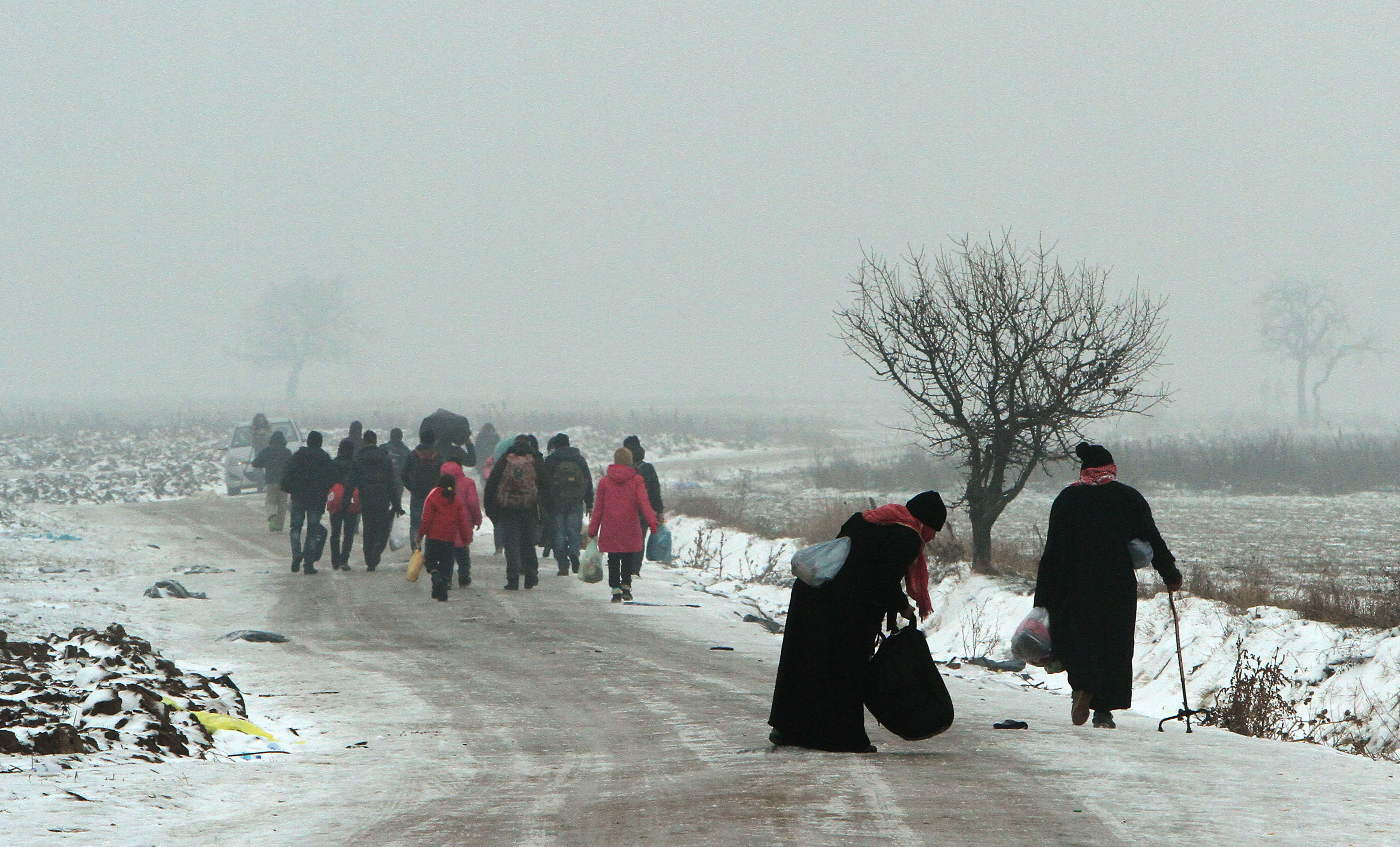 People of all ages brave the snow and cold weather as they try to reach a refugee camp on Tuesday in the Serbian village of Miratovac near border between Serbia and Macedonia [Djordje Savic/EPA]