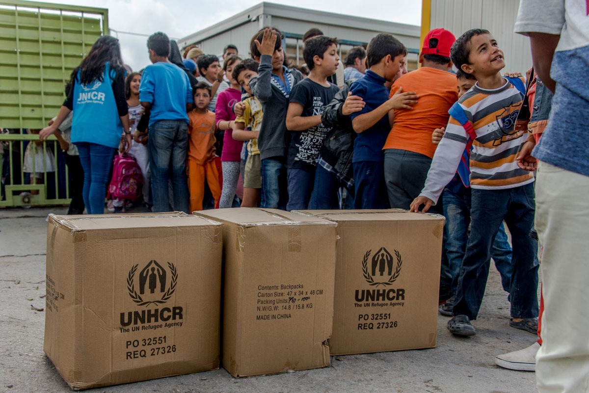 Refugee children wait in line to receive backpacks for their first day of school. [Dimitris Sideridis/Al Jazeera]