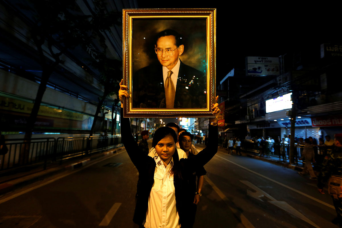 A woman poses with a portrait of Thailand's King Bhumibol Adulyadej, as others line up to hold the portrait after the announcement of the king's death, outside Siriraj Hospital in Bangkok. The world's longest-reigning monarch died at the age of 88 on October 13. [Jorge Silva/Reuters]