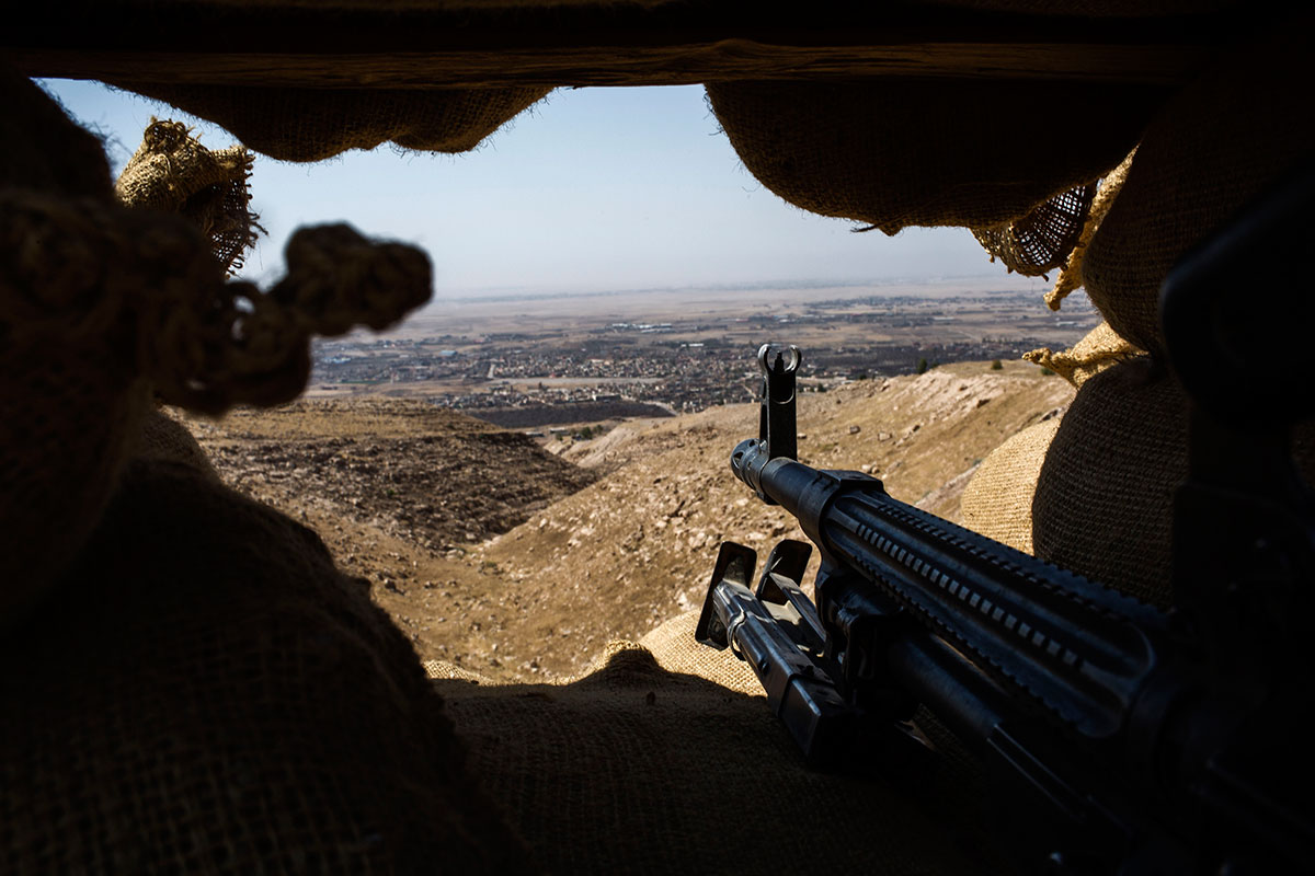Bashiqa city is seen though a trench in the mountains. [Diego Ibarra Sanchez/MeMo/Al Jazeera]