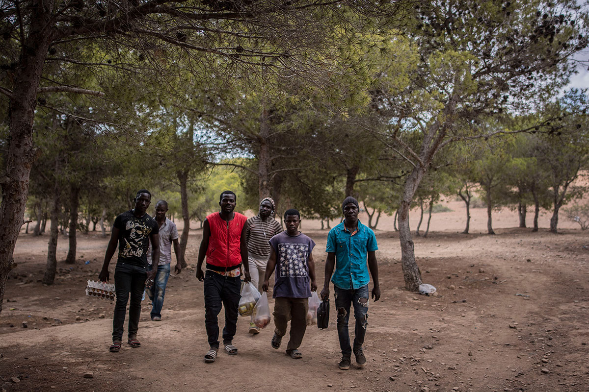 A group of men arrive with food at the entrance to the Bolingo camp. To obtain basic supplies, they must walk almost 2km to Selouane, the closest village. [Maria Contreras Coll/Al Jazeera]