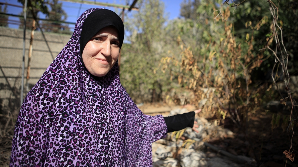 Enas Taha shows her garden, which has turned brown due to the severe water shortages since June [Eloise Bollack/Al Jazeera]