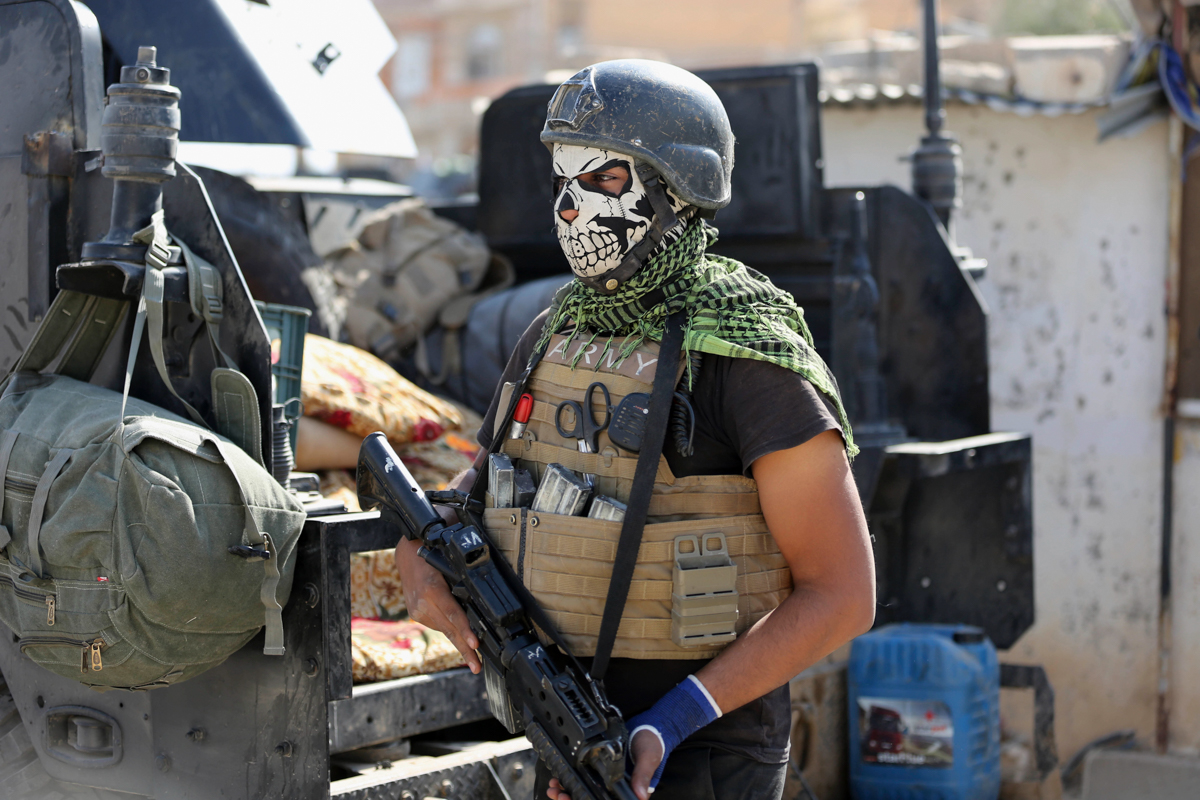 A member of Iraq's elite counterterrorism forces stands guard in the town of Bartella, Iraq. Iraqi forces have captured Bartella, around 15km east of Mosul. [Khalid Mohammed/AP]