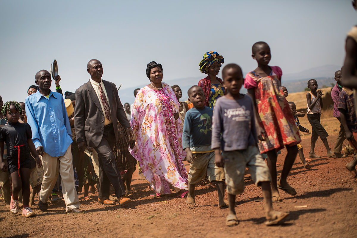 A Congolese couple walk with their friends and family to the tent where the weddings will take place. [Griff Tapper/Al Jazeera]