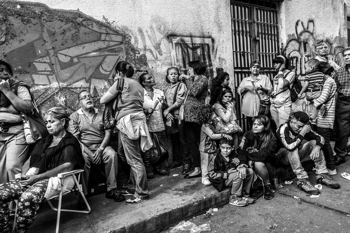 People line up for hours to buy basic products in front of a supermarket in La Candelaria district. [Alessandro Falco/Al Jazeera]