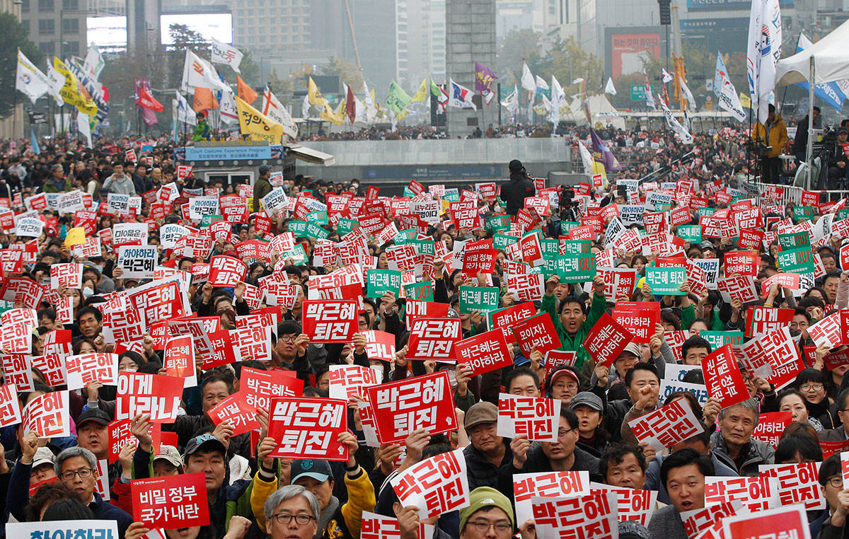 "Tens of thousands of South Koreans poured into the streets of Seoul on Saturday to demand that President Park Geun-hye step down amid an explosive political scandal involving and old friend of the president. The signs read ""Park Geun-hye should step down"". [Ahn Young-joon/AP]"
