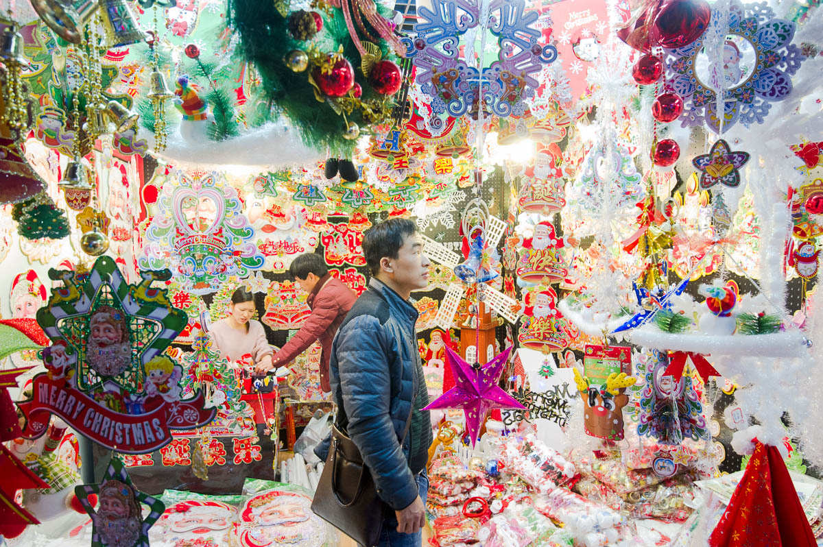 Potential customers examine Christmas decorations on offer at a booth in the Festival Arts section of