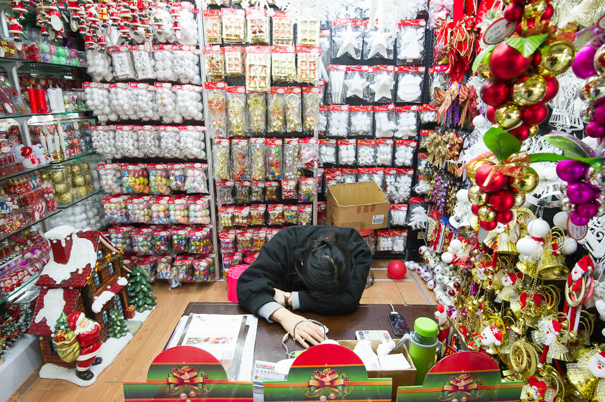 a vendor sleeps behind a desk in a stall of christmas decorations inside the festival arts