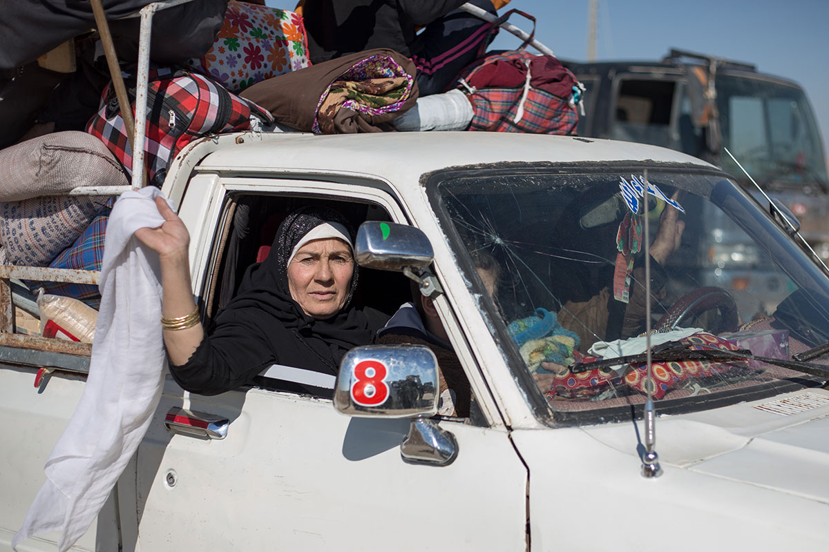 A woman waves a white flag from a heavily-laden pick-up truck as it approaches an Iraqi army checkpoint near the town of Bazwaya on Mosul's eastern outskirts. Thousands have fled heavy fighting there in recent days as Iraqi forces pushed further into the city. [John Beck/Al Jazeera]
