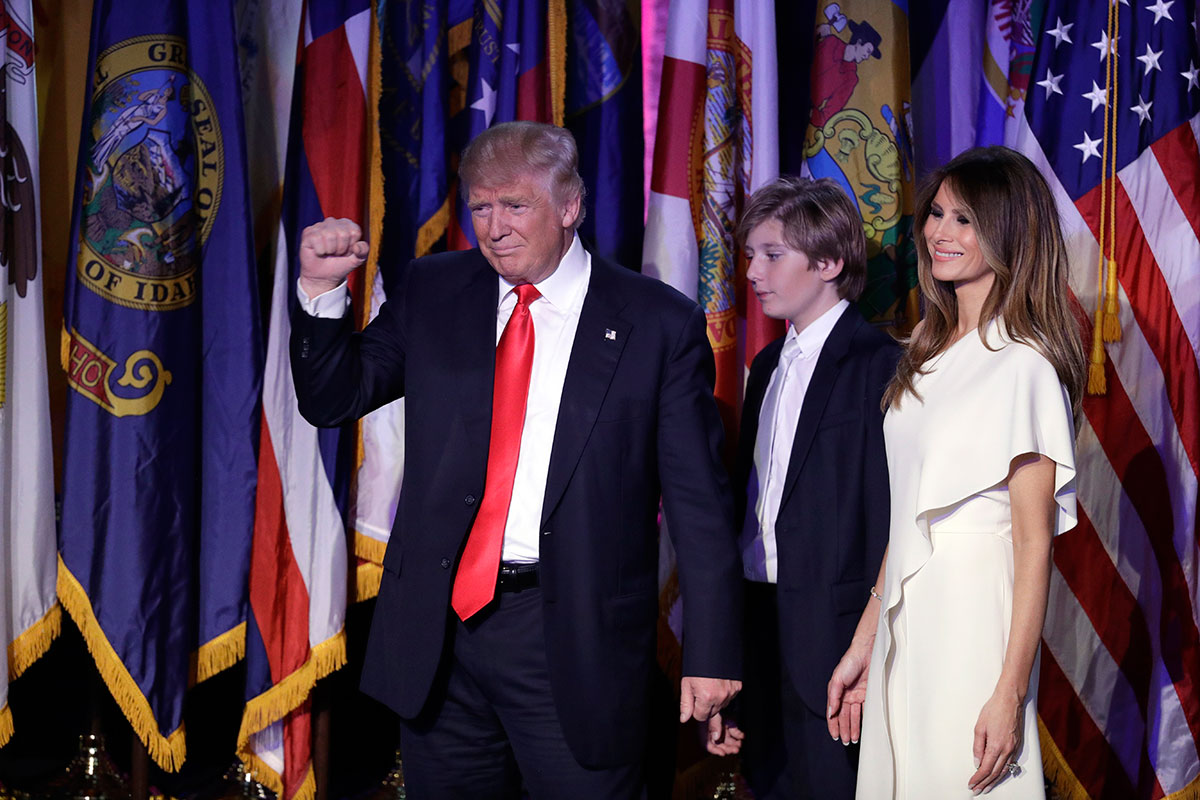 President-elect Donald Trump pumps his fist after giving his acceptance speech as his wife Melania Trump, right, and their son Barron Trump follow him during his election night rally in New York. [John Locher/AP]