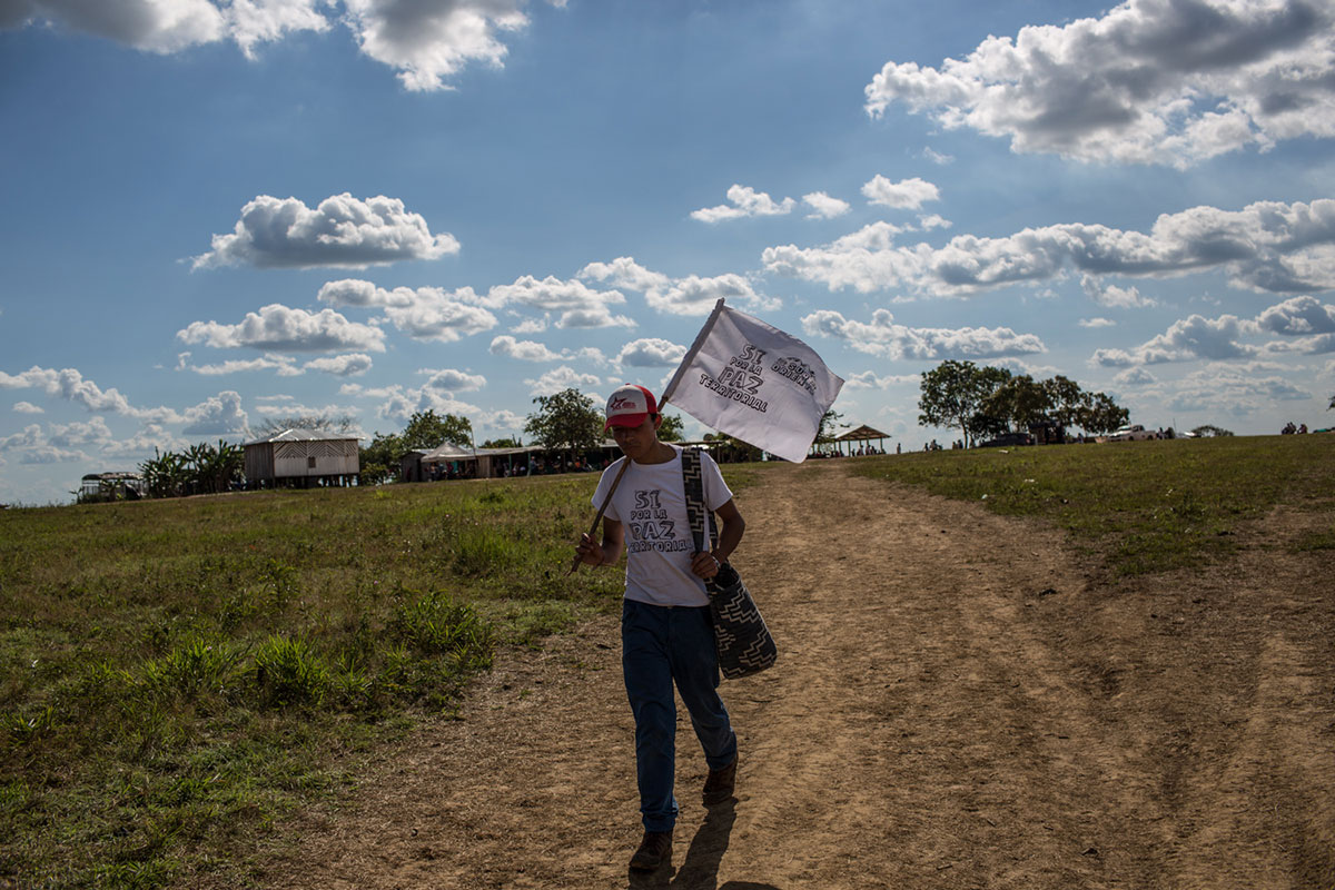 A vigil attendee arrives at a FARC camp in the Yari plains area carrying a white flag. People gathered at the vigil were from other regions as well as from the capital, Bogota. [Mauricio Morales/Al Jazeera]