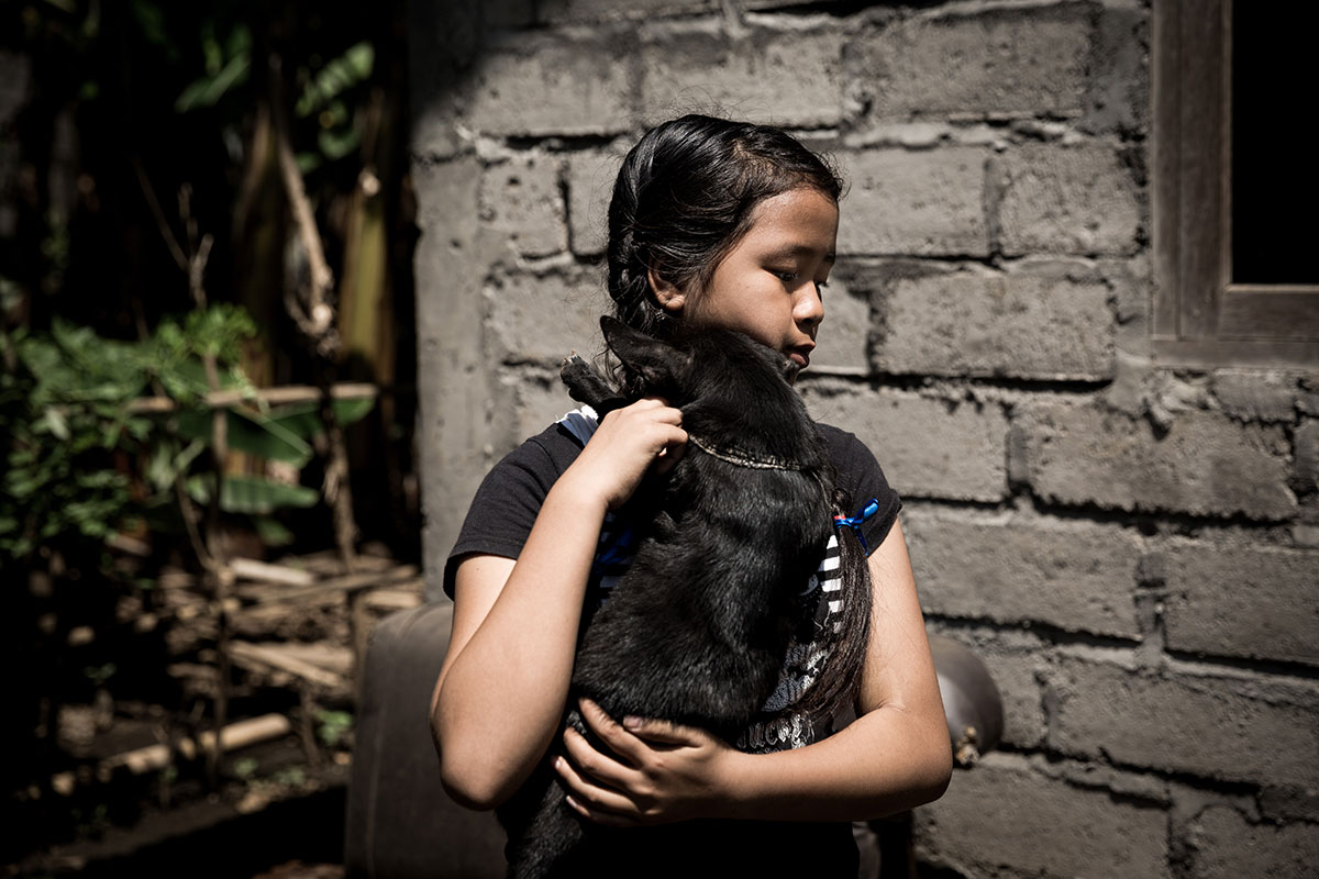 Agung Dewi hugs Selip, the black dog that she believes saved her life when she was in hospital with food poisoning two years ago. [Agung Parameswara/Al Jazeera]
