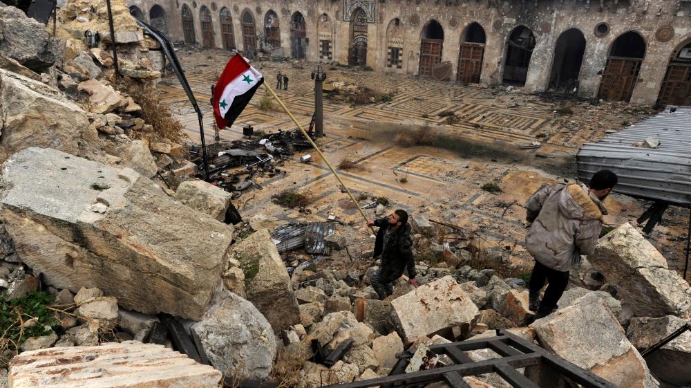 Un soldato siriano sventola la bandiera nazionale sulle macerie della moschea degli Omayyadi ad Aleppo. Credits to: Omar Sanadiki/Reuters