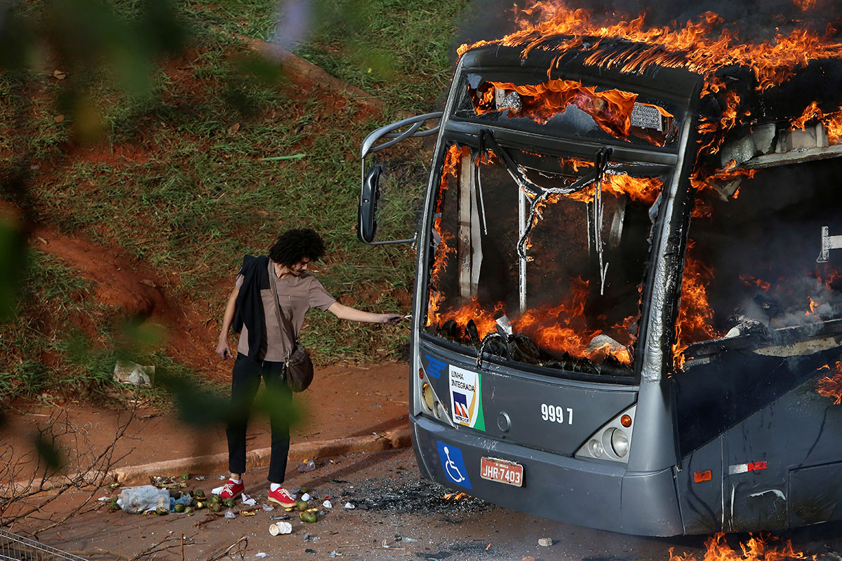 A man lights up his cigarette with the flames of a bus burned by Brazilian anti-government demonstrators during a protest in front of the National Congress in Brasilia against a constitutional amendment that limits public spending. [Adriano Machado/Reuters]