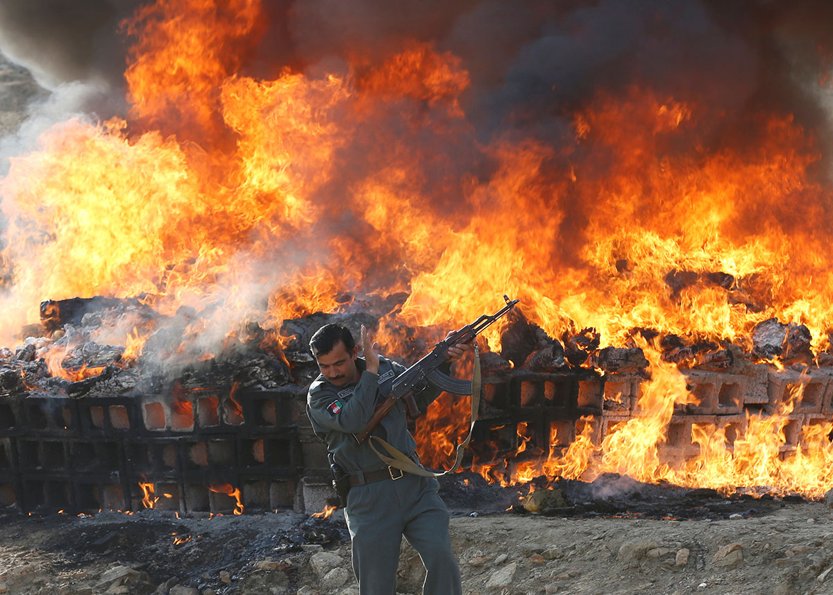 An Afghan officer in front of a burning pile of seized narcotics and alcoholic drinks, on the outskirts of Kabul, Afghanistan. Officials set fire to 98 tonnes of opium, heroin, hashish and alcoholic drinks. [Omar Sobhani/Reuters]