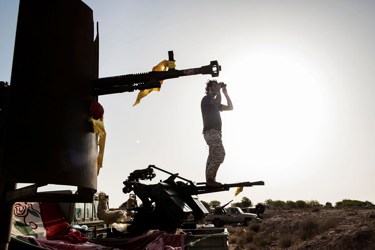 Standing on the barrels of a heavy machinegun, a fighter from Libya's Government of National Accord watches ISIL positions in Sirte. [Alessio Romenzi/CAPTA/Al Jazeera]