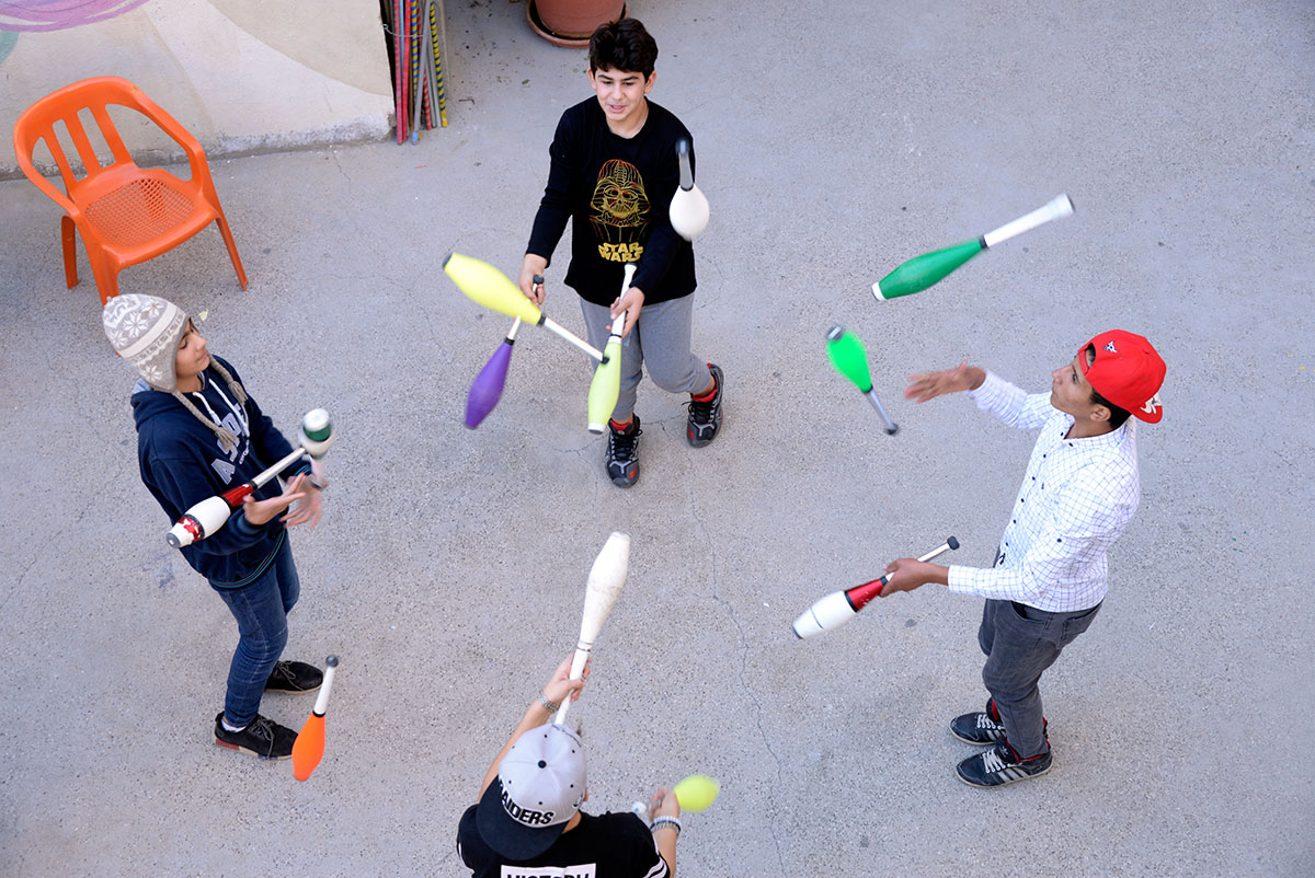 Four boys juggle clubs in a circle, putting their teamwork and eye-to-hand coordination skills to work. Dozens of refugee children living near Mardin have benefited from the programme over the past five years. [Didem Tali/Al Jazeera]