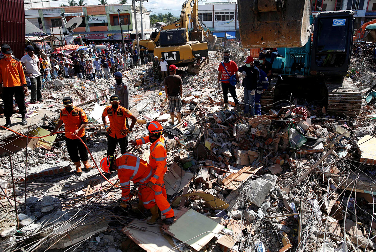 Rescue teams use heavy equipment to dig through a collapsed building following a strong earthquake in Meureudu market, Pidie Jaya, Aceh province, Indonesia. [Darren Whiteside/Reuters]