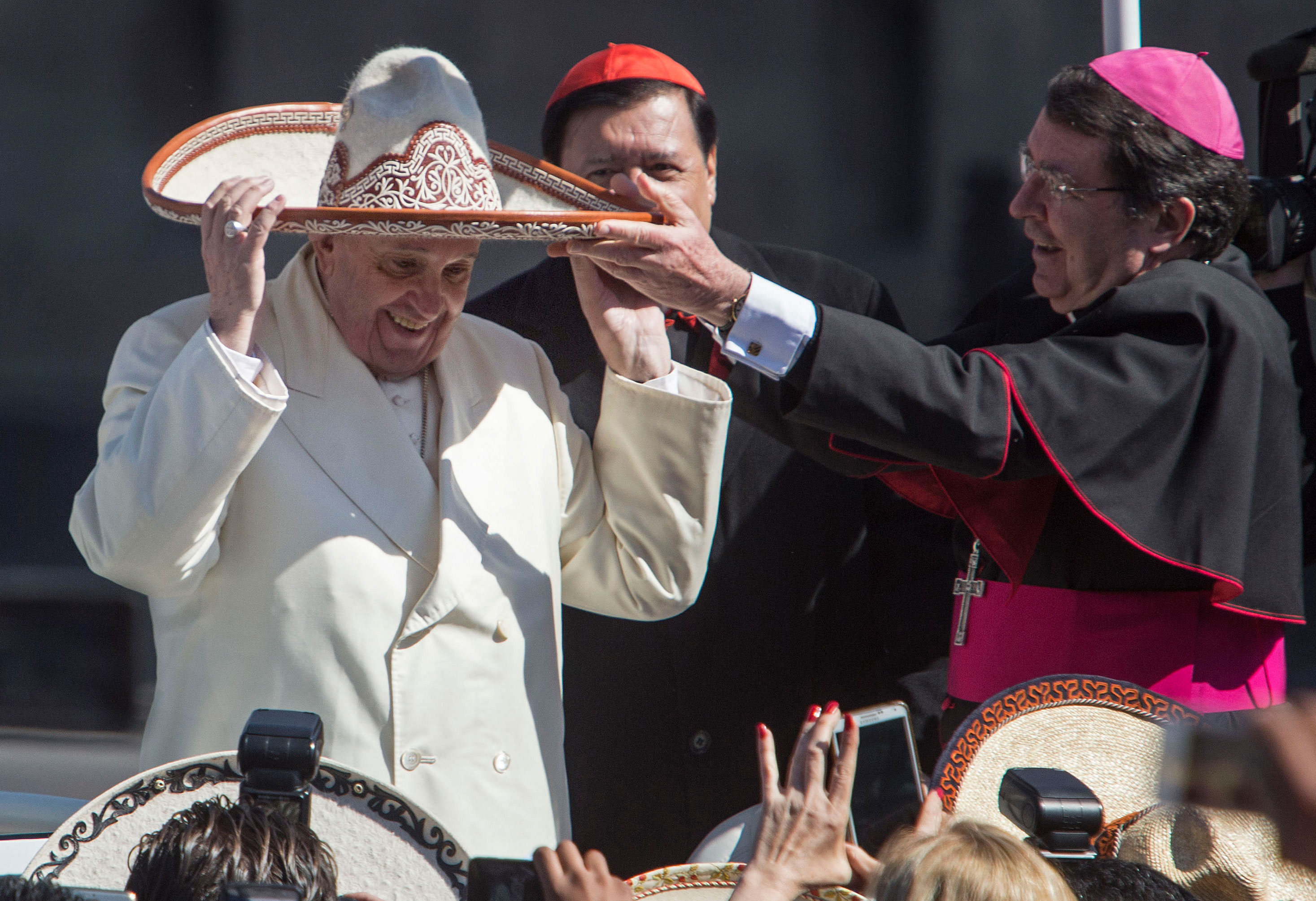 Pope Francis tries on a Mexican Charro sombrero given to him by a person in the crowd in Mexico City's main square, the Zocalo. [Christian Palma/AP]