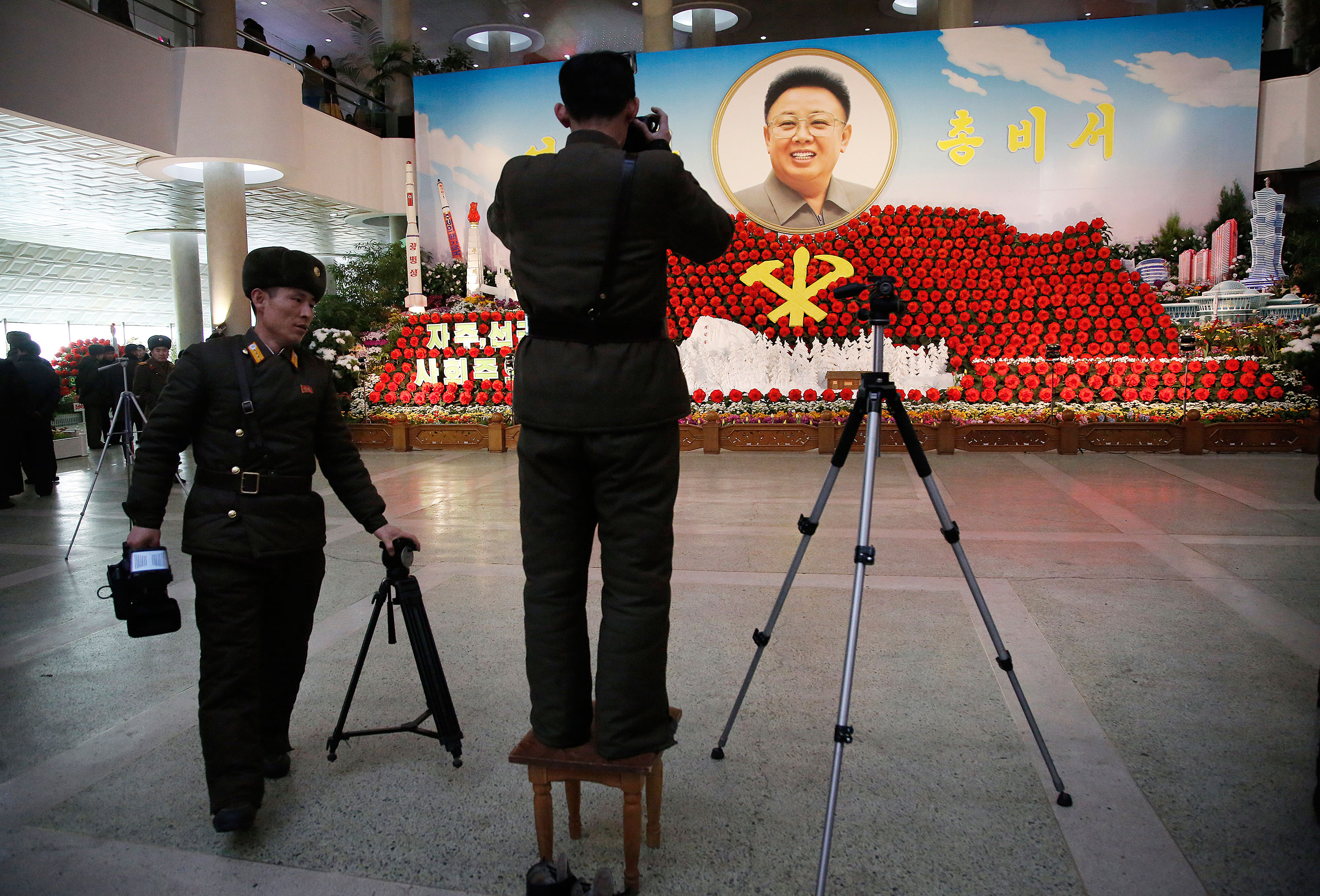 North Korean soldiers take photos of a portrait of their late leader Kim Jong Il at a flower festival with a model of North Korea''s newest satellite Kwangmyongsong 4, left, on display as part of the celebrations. [Wong Maye-E/AP]