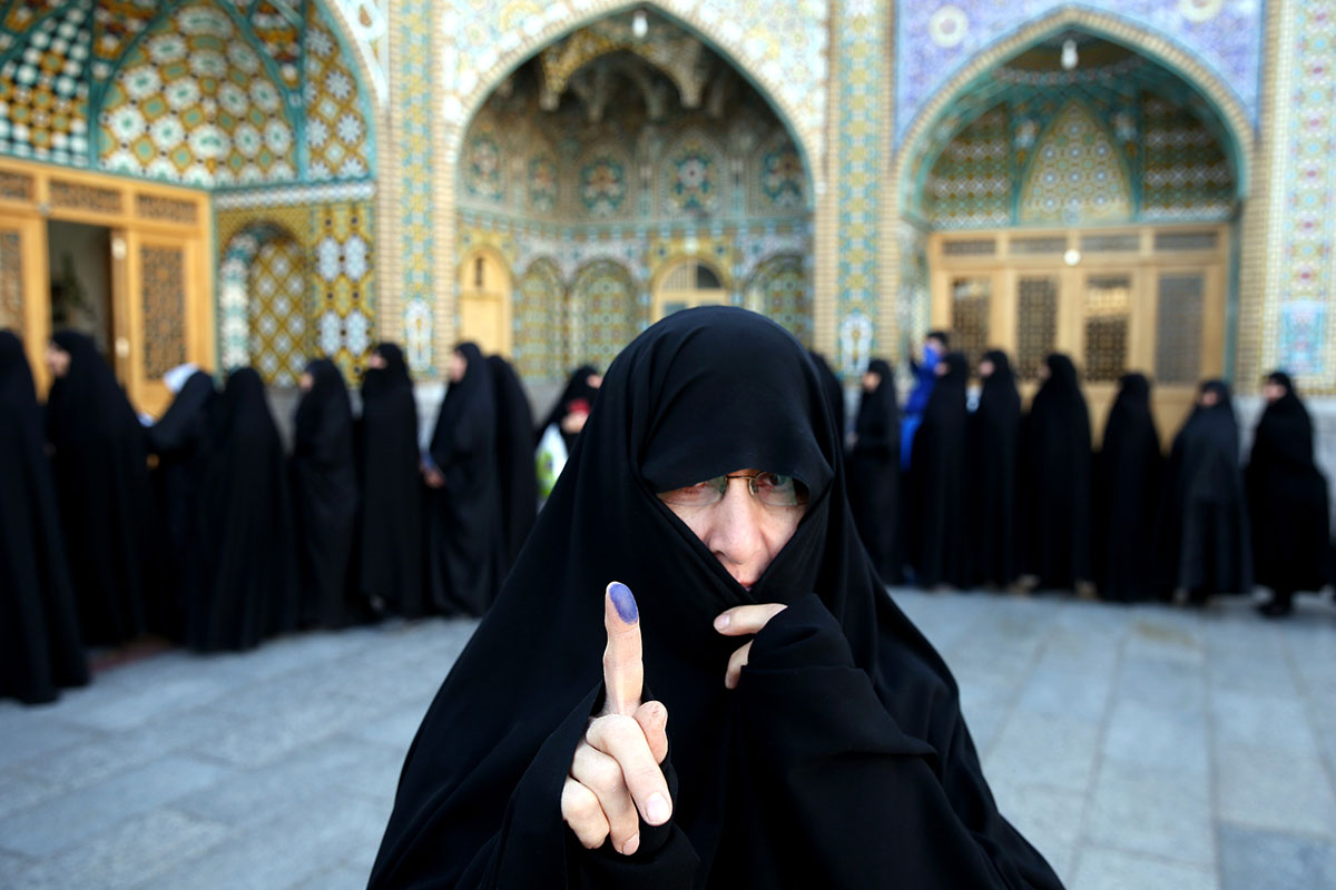 An Iranian woman displays her ink-stained finger after voting at a polling station in Qom, 125km south of Tehran, on Friday. [Ebrahim Noroozi/AP]
