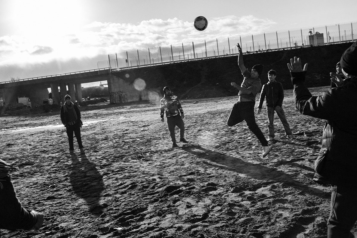 Afghan refugees playing volleyball at the makeshift camp in Calais. [Fabio Bucciarelli/MeMo/Al Jazeera]