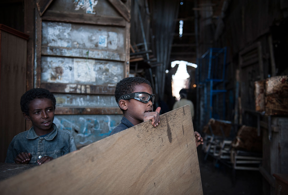 A young boy works at an outdoor welding factory and metal market called Medeber, in Asmara. Every available item is used and recycled with bits of old machinery being hammered, cut, welded, formed and turned into something of use. Eritreans pride themselves on their self-reliance. March 2013. [Didier Bizet/Al Jazeera]