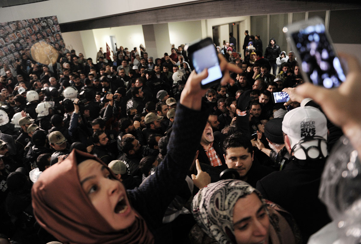 Journalists react as riot police enter the headquarters of Turkey's largest-circulation newspaper Zaman in Istanbul, Friday, March 4, 2016. The police raid came hours after a court placed it under the management of trustees on Friday. The move against the paper, which is linked to an opposition cleric, heightened concerns over deteriorating press freedoms in the country. [AP]