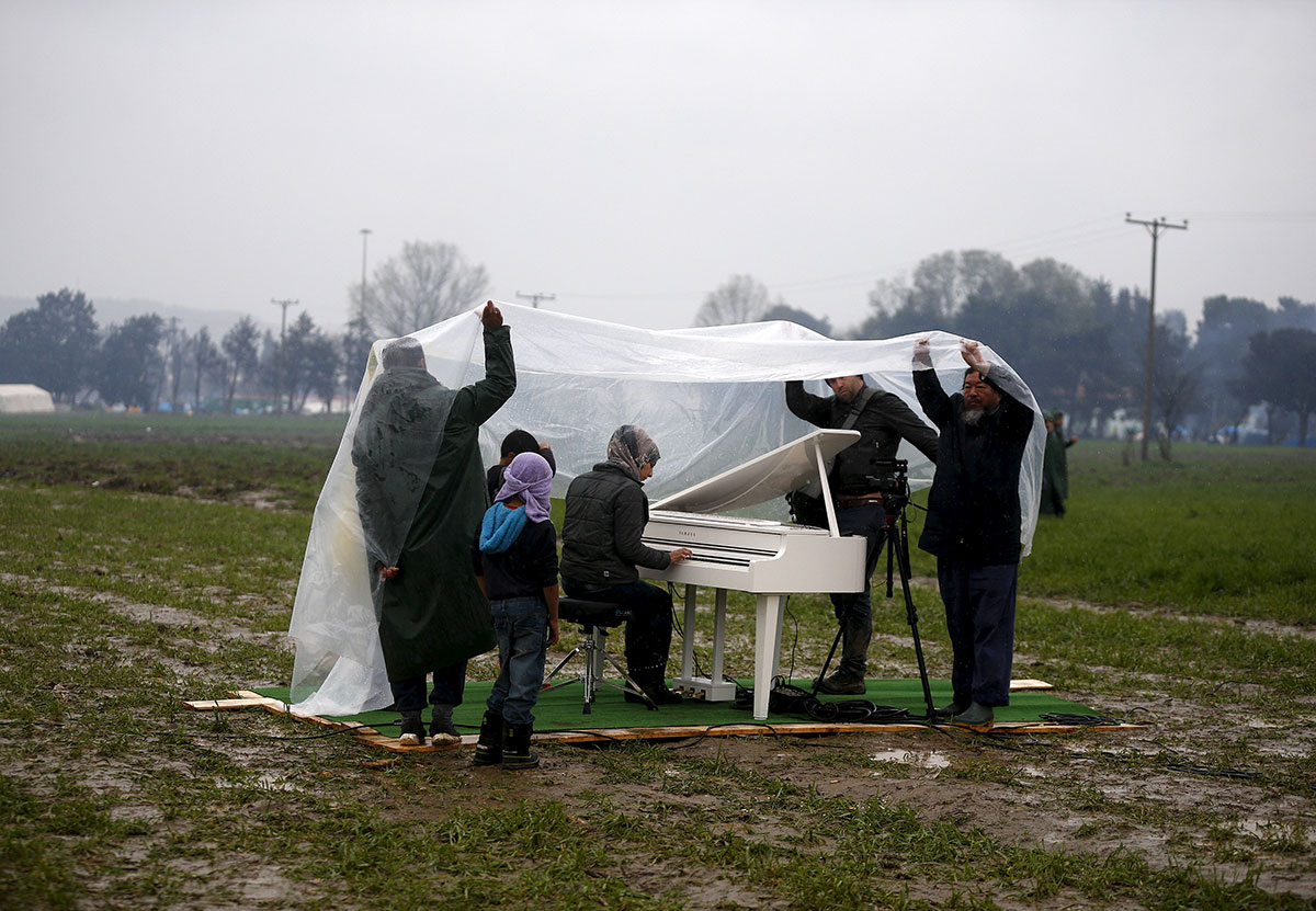 Chinese artist and activist Ai Weiwei (right) films a Syrian refugee woman playing a piano near a makeshift camp in Idomeni on the Greek-Macedonian border. [Stoyan Nenov/Reuters]