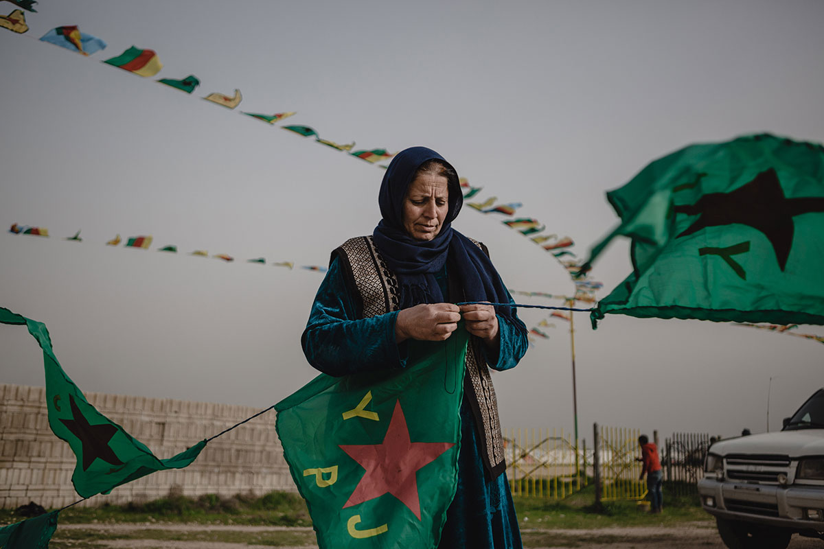 A women sews Kurdish People's Defence Units flags in Amude, Syria. The flags are for Newroz celebrations organised by the Democratic Union Party. [Andrea DiCenzo/Al Jazeera]