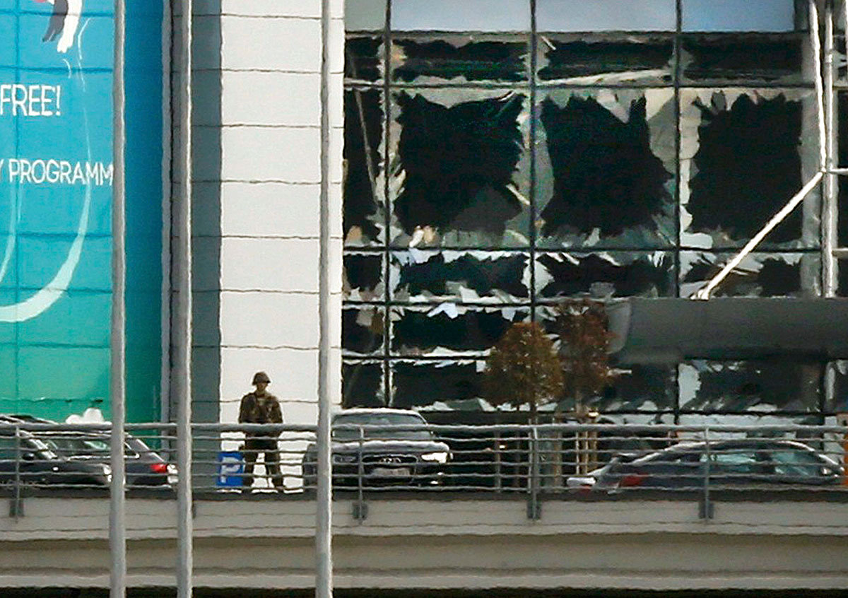 A soldier stands near broken windows after explosions at Zaventem airport on the outskirts of Brussels, Belgium. [Francois Lenoir/Reuters]