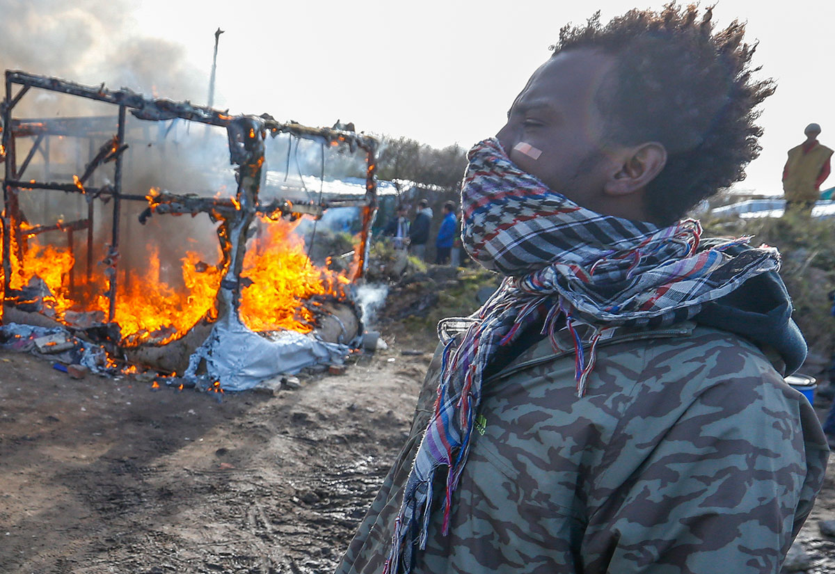 "Migrants stand near a burning makeshift shelter set ablaze in protest against the partial dismantlement of the camp for migrants called the ""Jungle"", in Calais, France [Yves Herman/Reuters]"