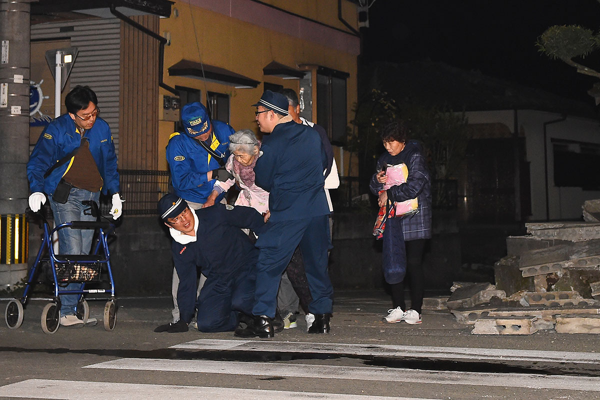 Rescue workers provide assistance to an elderly woman after the earthquake on April 14, 2016 in Mashiki, Kumamoto, Japan. A powerful earthquake with a preliminary magnitude of 6.2 struck Kumamoto Prefecture. [Masterpress/Getty Images]