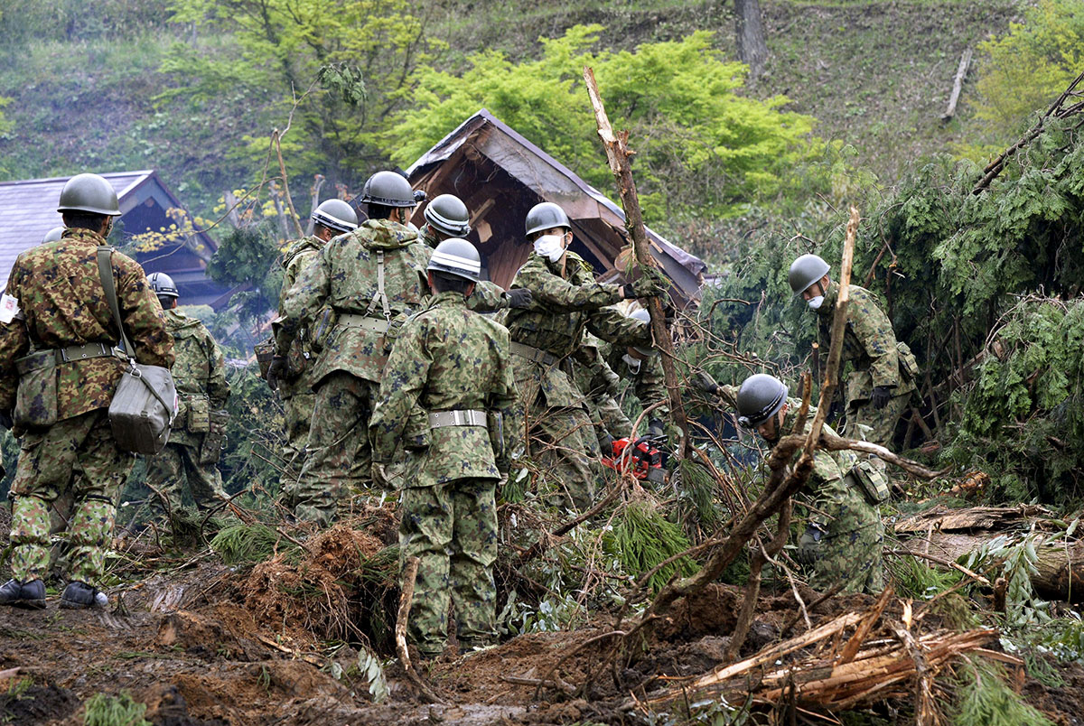 Japan Ground Self-Defence Force soldiers conduct search and rescue operations for a missing guest at a destroyed mountain villa following a landslide site caused by an earthquake in Minamiaso town, Kumamoto prefecture, southern Japan. [Kyodo/Reuters]