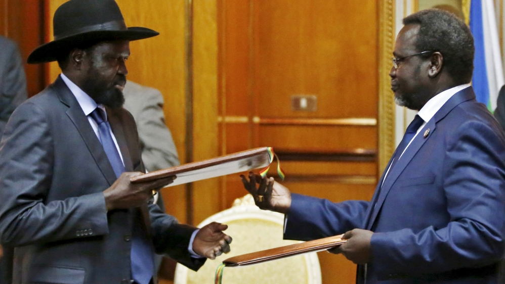 File photo shows South Sudan's rebel leader Riek Machar and South Sudan's President Salva Kiir exchanging signed peace agreement documents in Addis Ababa