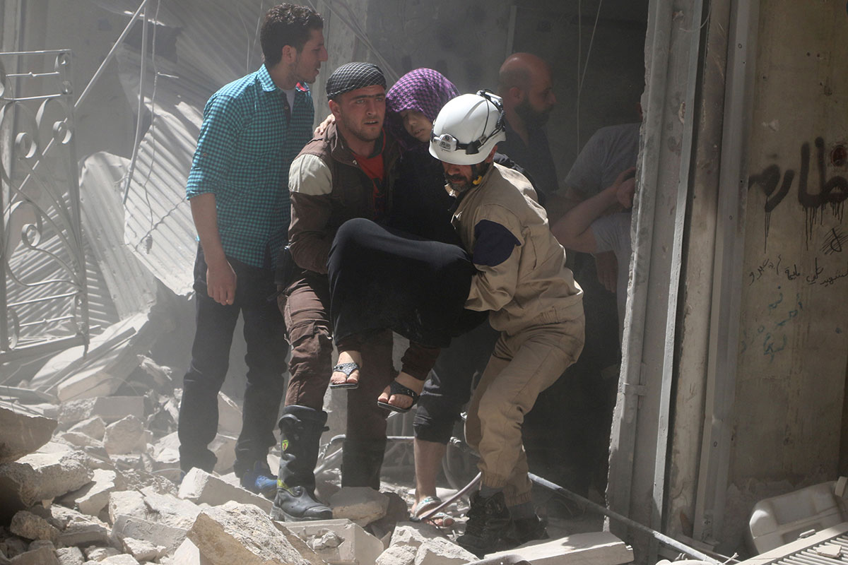 Civil defence members evacuate a woman from a damaged building after air strikes in the rebel-held area of old Aleppo. [Abdalrhman Ismail/Reuters]