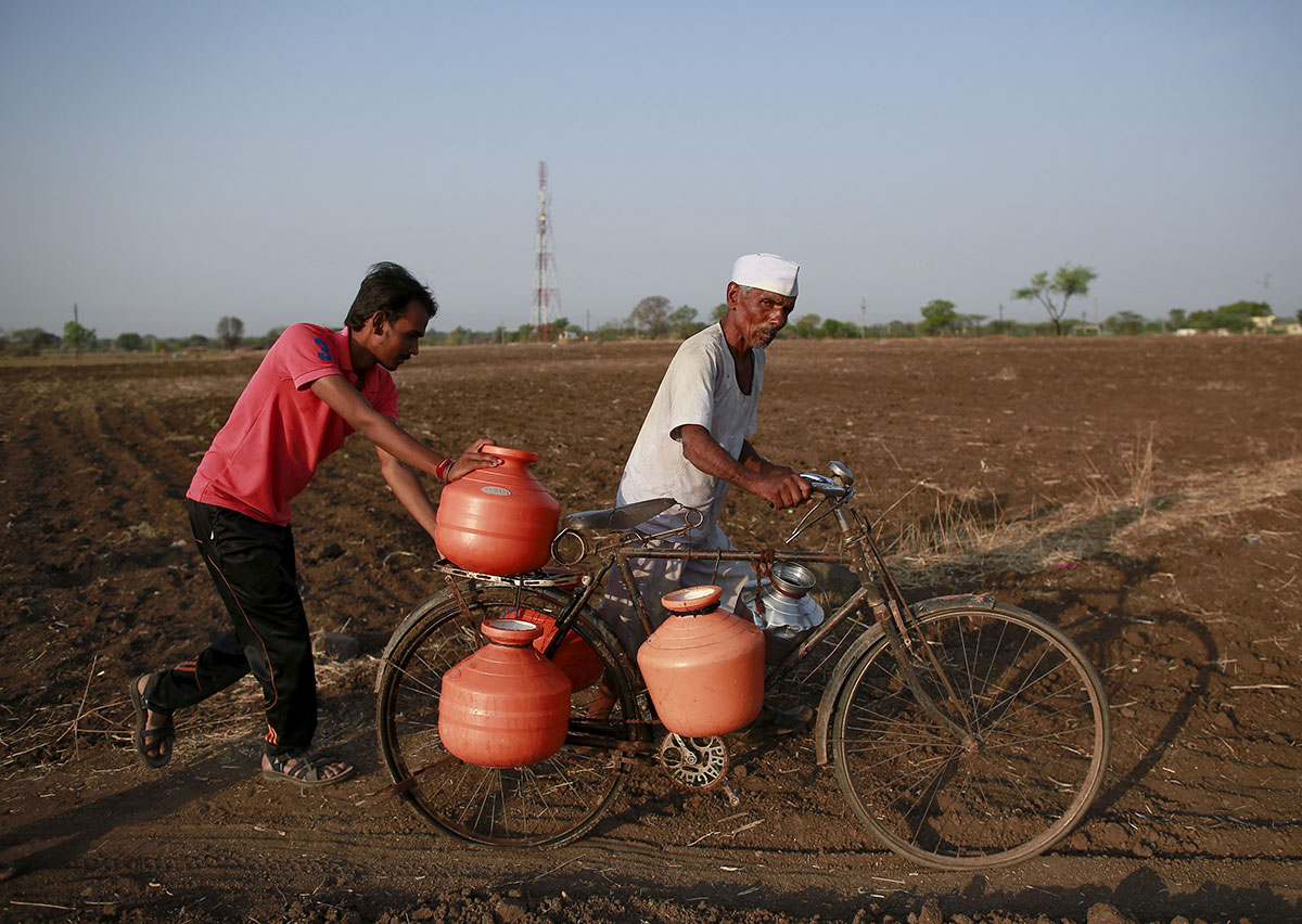 Residents push a bicycle loaded with water containers through a field in Western India's Latur district. About 330 million people, almost a quarter of the country's population, are facing the worst drought in four decades. [Danish Siddiqui/Reuters]