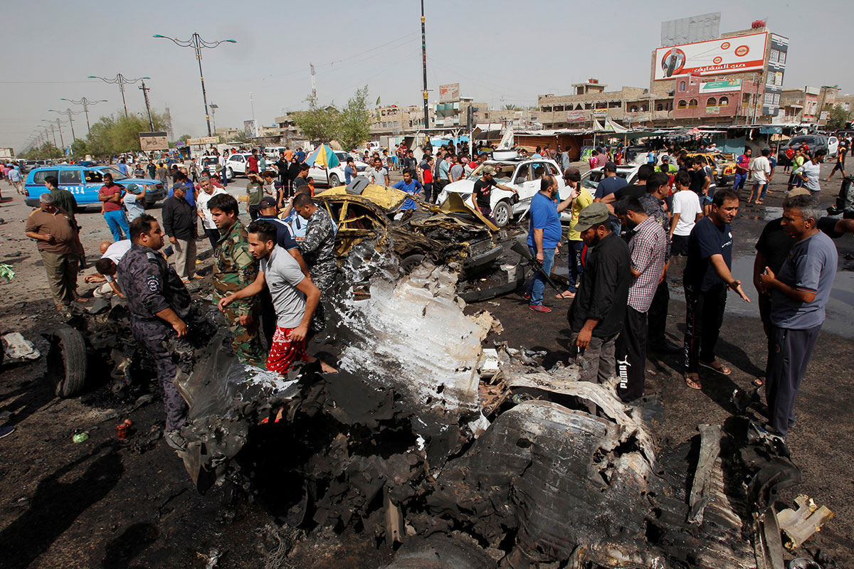 Iraqi security forces and bystanders gather at the site of a car-bomb attack in Baghdad's mainly Shia district of Sadr City. [Khalid al Mousily/Reuters]