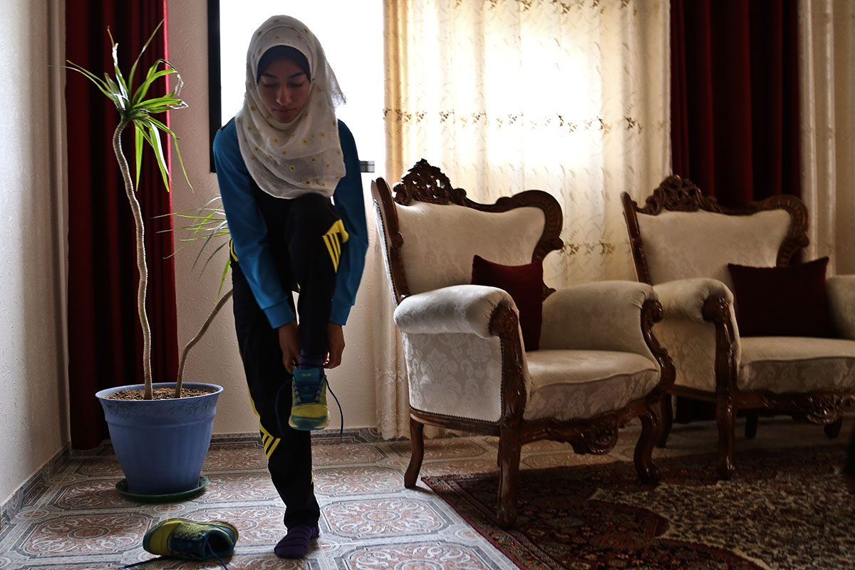 Inas Nofal runs every day, and sometimes even twice a day, she says. Her coach, Sami Nateel al-Balad, buys all of her shoes. 'It's rare to find appropriate running shoes here, so as soon as I come across a pair, I buy them for her. To be professional is expensive and you need sponsors, but that isn't possible here.' [Lena Odgaard/Al Jazeera]