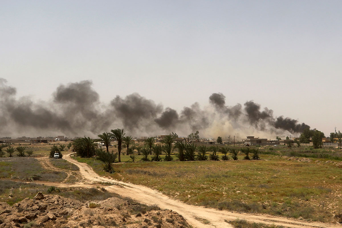 Smoke rises from Islamic State of Iraq and the Levant (ISIL) positions at the frontline during fighting outside Fallujah. [Khalid Mohammed/AP]