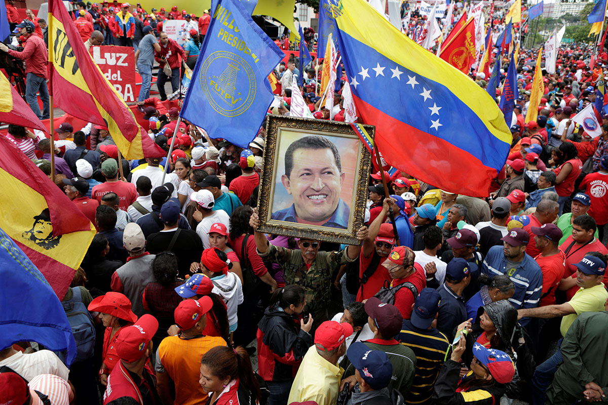 A supporter of Venezuela's President Nicolas Maduro holds a portrait of Venezuela's late President Hugo Chavez, during a rally to commemorate May Day, in Caracas, Venezuela. [Marco Bello/Reuters]